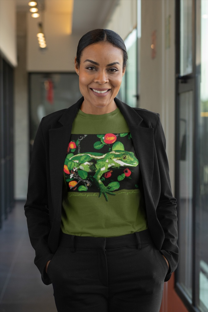 A professional woman posing in a military green jewelled gecko t-shirt at the office.