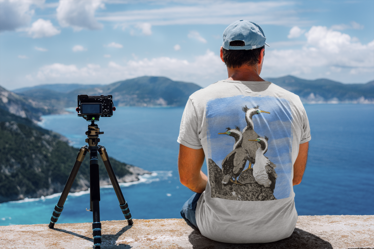 Back view of a man enjoying the landscape wearing a silver-grey spotted shags two-sided t-shirt.