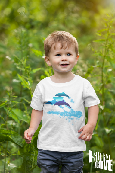 A toddler wearing a dolphin t-shirt and walking in nature.
