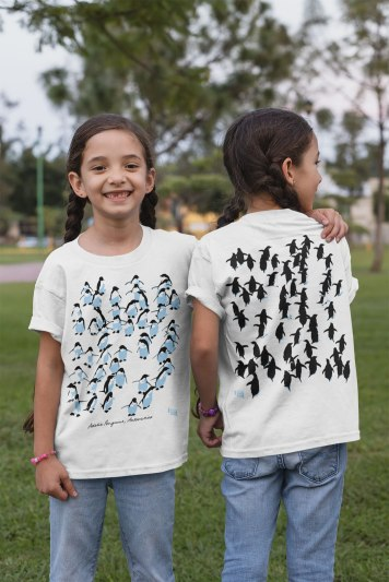 twin girls wearing Adelie penguins t-shirts showing front and back print in a park