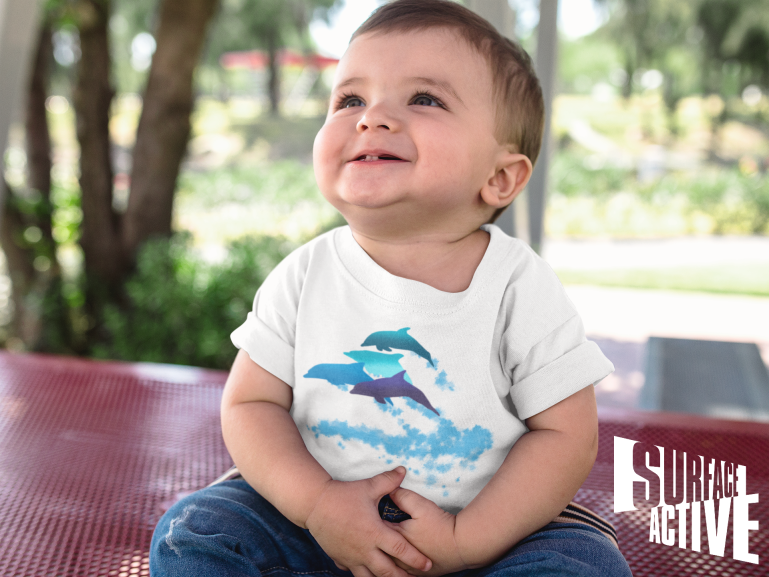 A baby boy looking up while smiling wearing a dolphin teeshirt.
