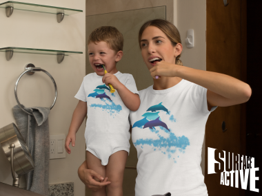 A dolphin onesie on a baby and his mum in a matching dolphin shirt while brushing their teeth