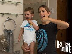 A dolphin onesie on a baby and his mum in a black paua t-shirt while brushing their teeth.