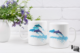 Two dolphin mugs by a floral centrepiece showing both sides of the mug design.