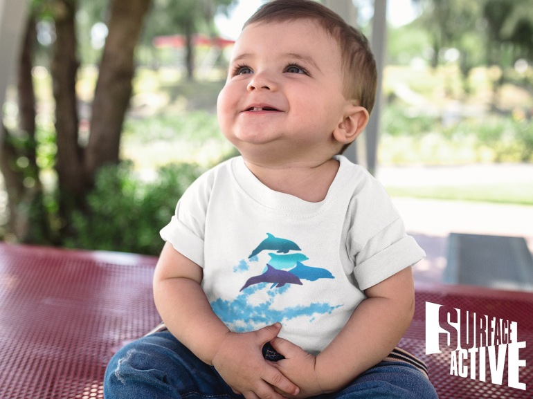 A baby boy looking up while smiling wearing a dolphins leaping New Zealand t-shirt.