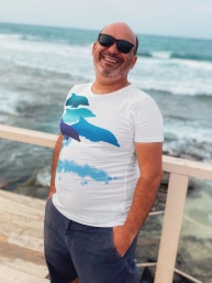 A happy middle aged man wearing a dolphins leaping New Zealand all-over printed t-shirt standing beside the sea.