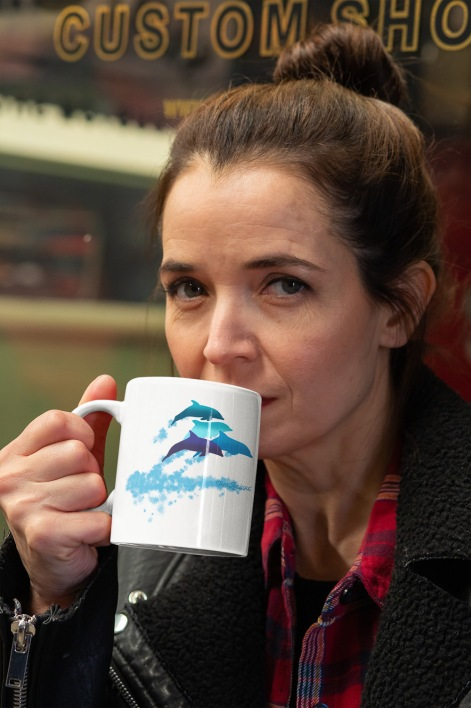 A serious woman drinking from an 11 oz dolphins leaping New Zealand mug while looking at the camera.