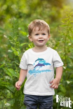 A toddler wearing a dolphins leaping New Zealand t-shirt and walking in nature.