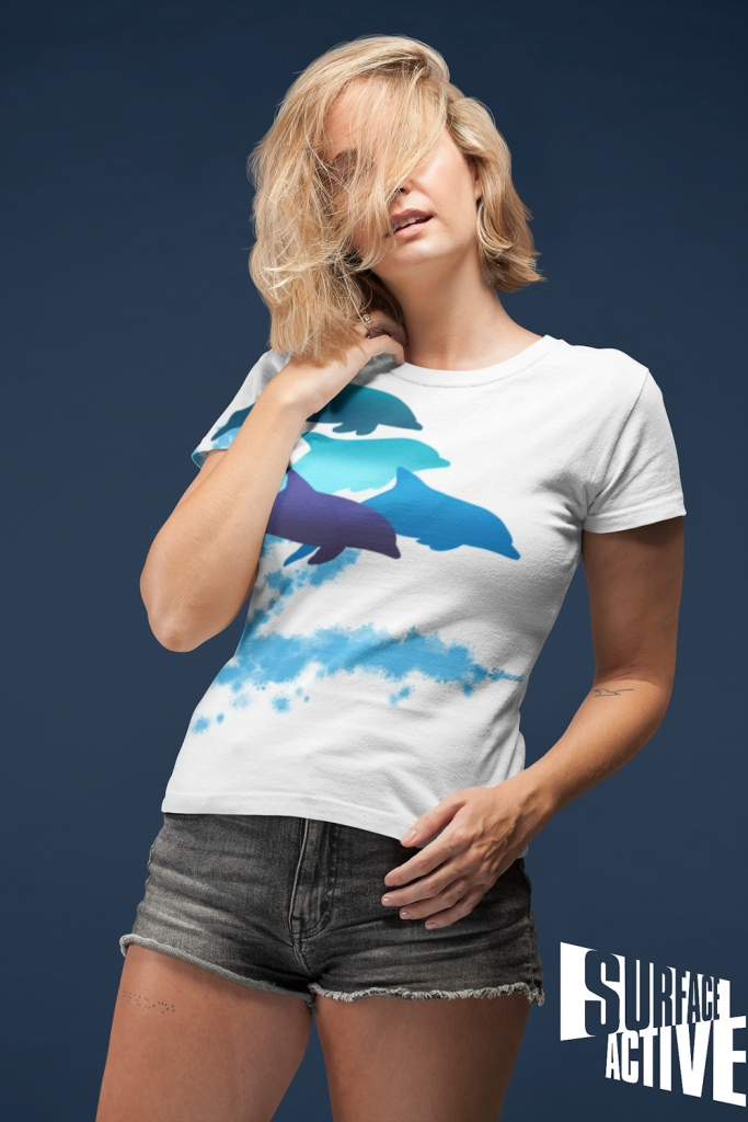 A woman wearing a dolphins leaping New Zealand all-over printed t-shirt with her hair all over her face.