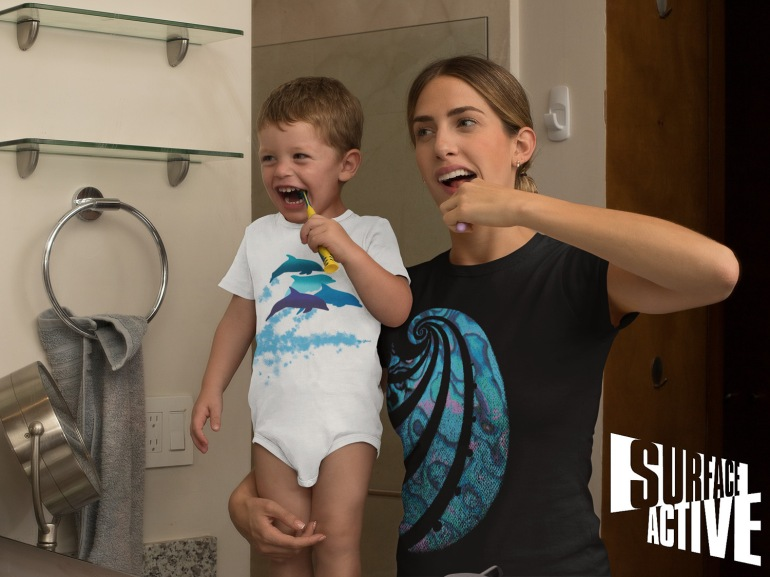 A dolphins leaping New Zealand t-shirt onesie on a baby with his mum wearing a paua pacific t-shirt while they brush their teeth.