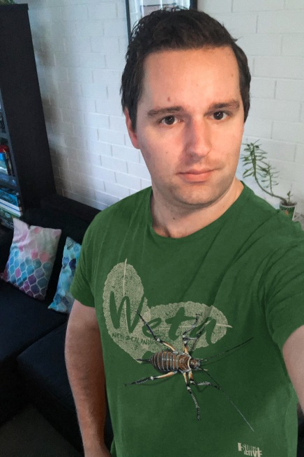Selfie of a man wearing a forest green weta, New Zealand t-shirt.