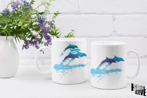 Two 11 oz dolphins leaping New Zealand mugs showing both sides of the two-sided design alongside a floral centrepiece.